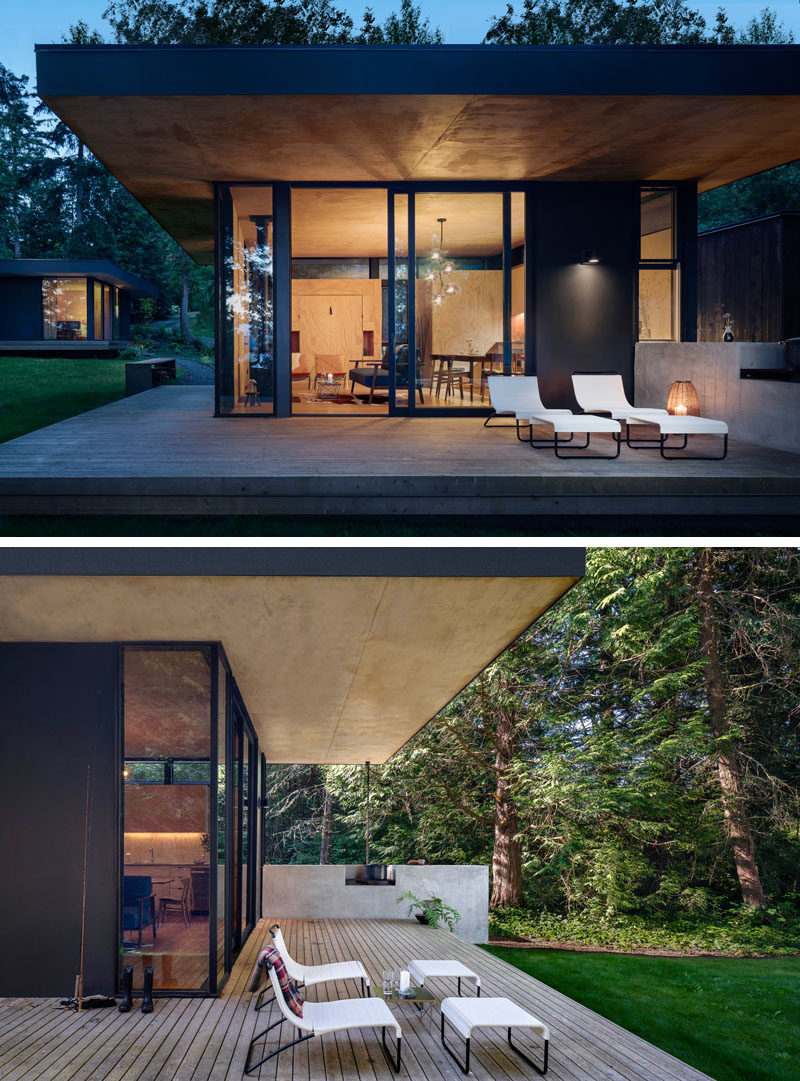 The design of this modern cabin include an indoor outdoor kitchen that has a pass-through window that extends the interior countertop into the outdoor concrete counter and built in wood barbeque.  #ModernCabin #KitchenDesign #OutdoorKitchen #BBQ