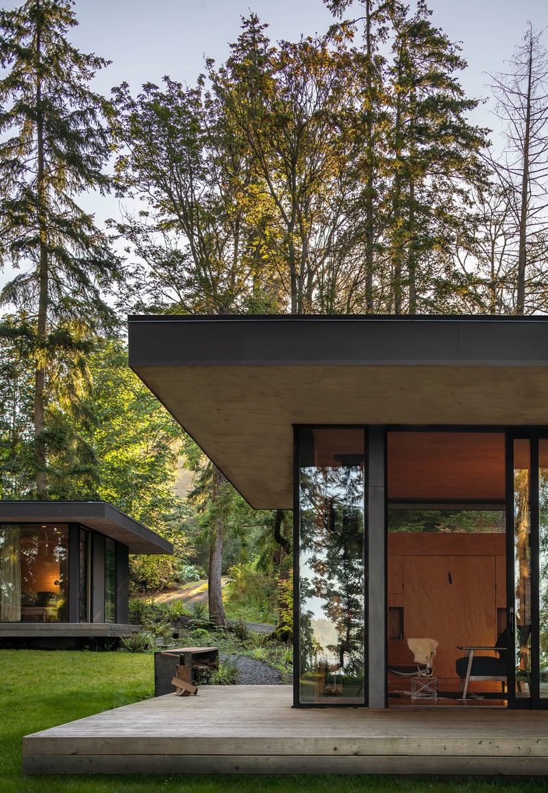 Rough sawn cedar siding and cement panel finishes on the exterior of these cabins will patina naturally over time until the cabin blends in with the colors of the forest. #ModernCabin #ModernArchitecture