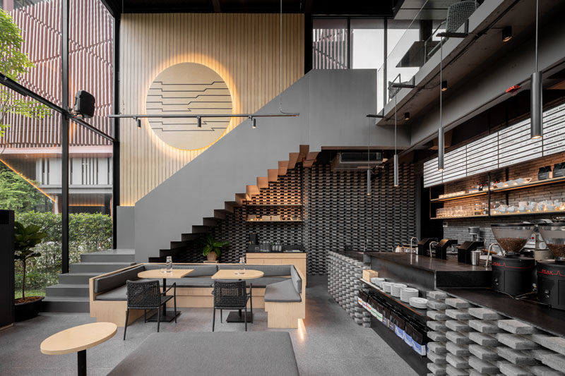 Inside this modern coffee shop, the high ceilings are immediately apparent, while wood and grey elements have been used to create a cozy atmosphere. #CoffeeShop #CafeDesign #RetailDesign #InteriorDesign