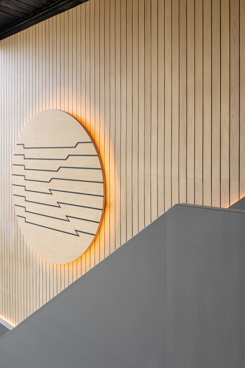 This modern coffee shop has a  tall wood-lined wall that's accented with a large wood disc, that also has a warm glow from the hidden lighting behind it. #CoffeeShopDesign #CoffeeShop #WoodWall