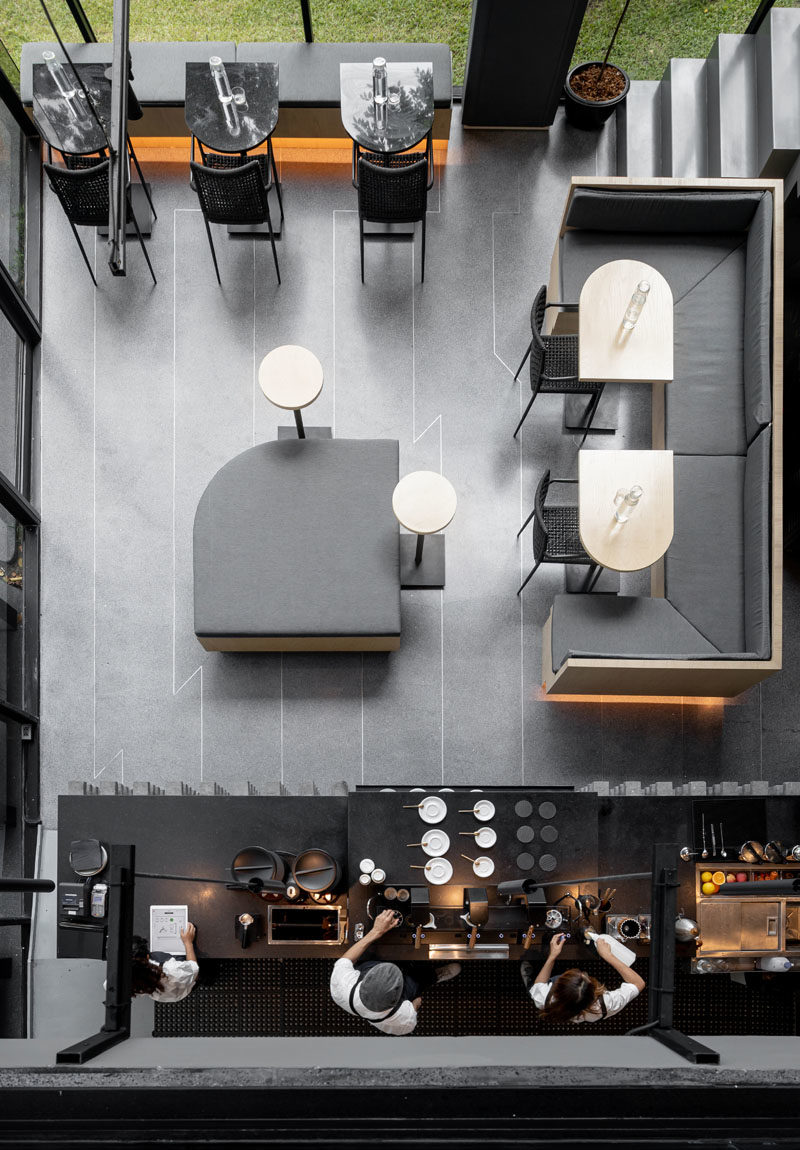 The main floor of this modern coffee shop is home to the service bar, where natural oak woods with rounded edges have been complemented by light grey cushions and banquettes. #CoffeeShop #ModernCafe #CoffeeShopDesign #InteriorDesign
