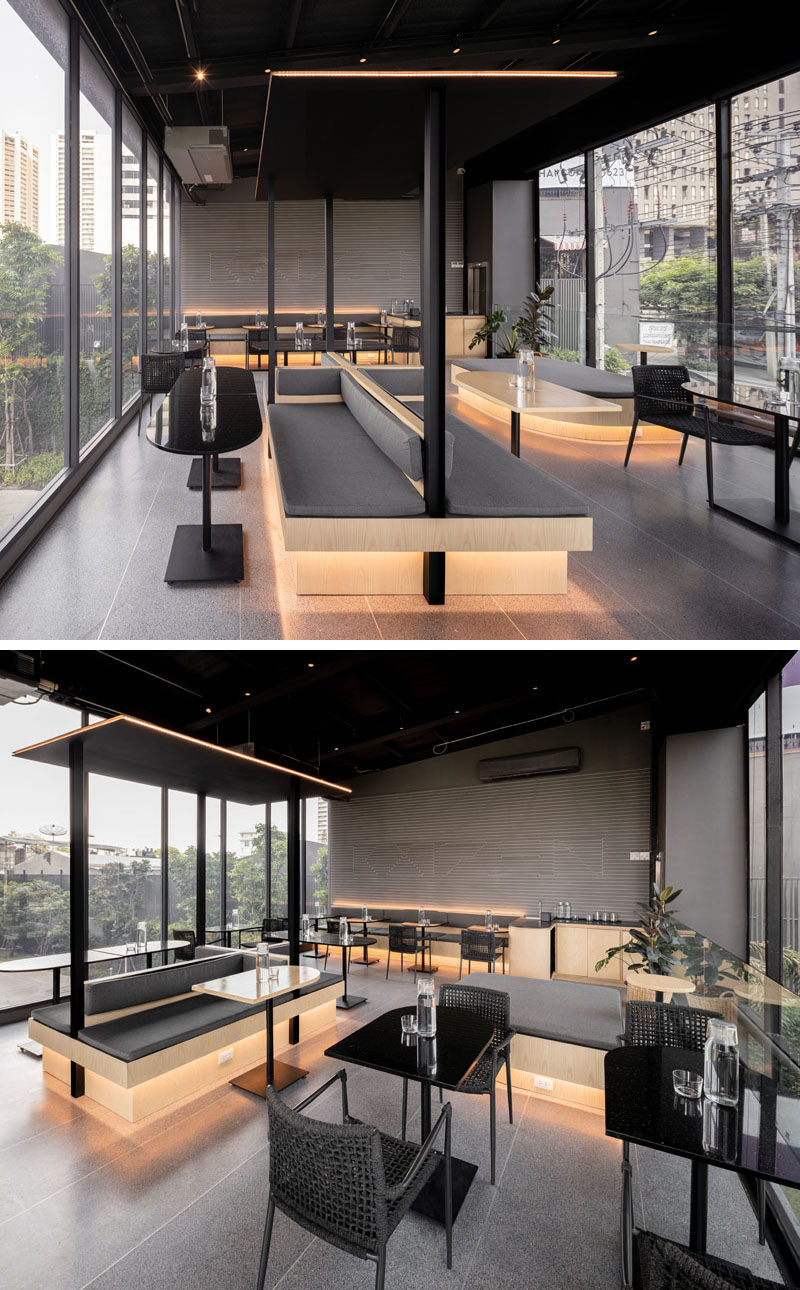 This modern coffee shop has hidden lighting underneath tables and behind the seating, creating a soft glow for the black, grey, and wood interior. #ModernCoffeeShop #CafeDesign #Lighting