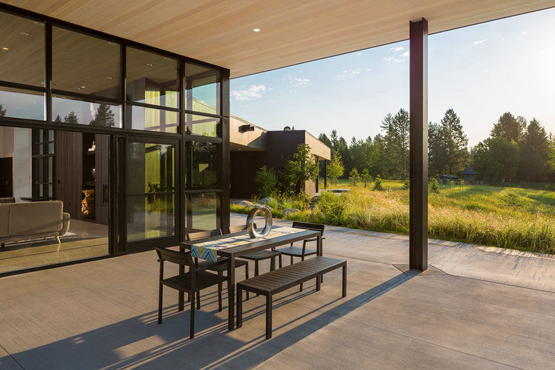 Glass doors off the living room of this modern house, slide open to reveal a covered patio with views of the surrounding landscape. #OutdoorSpace #Patio #Architecture
