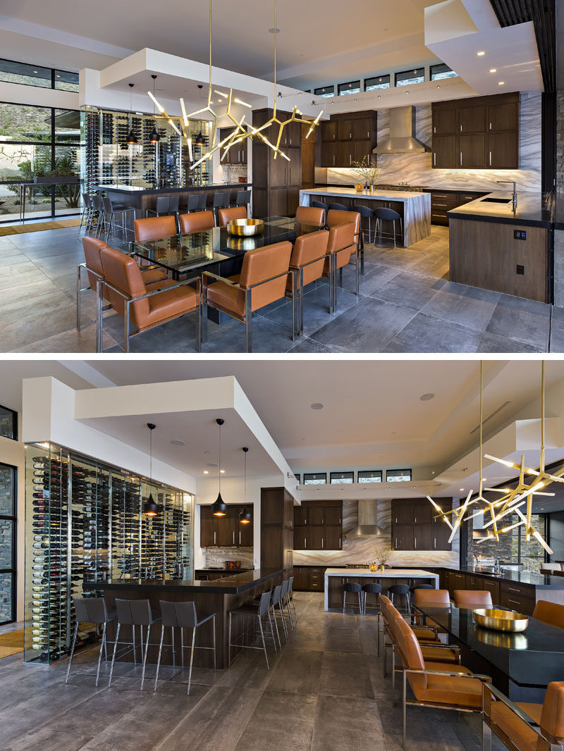 This modern dining room, with its sculptural chandelier, shares the open room with the kitchen and a bar, that also features a built-in glass wall that provides wine storage. #ModernDiningRoom #ModernKitchen #KitchenDesign #Bar #WineStorage