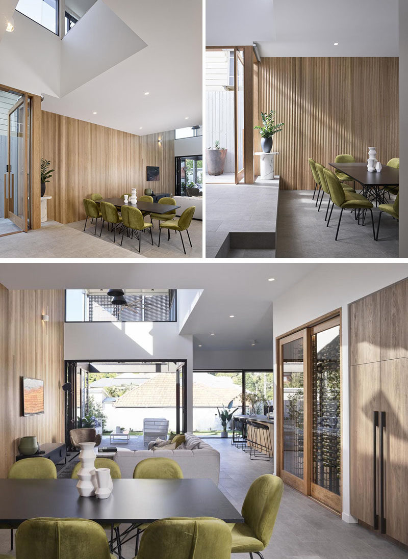 Dining Room Ideas - The front door of this modern house opens to a large open plan interior with double-height voids. A couple of steps lead down to the dining area that features olive green chairs surrounding a dark dining table #DiningRoomIdeas #ModernDiningRoom #WoodAccentWall