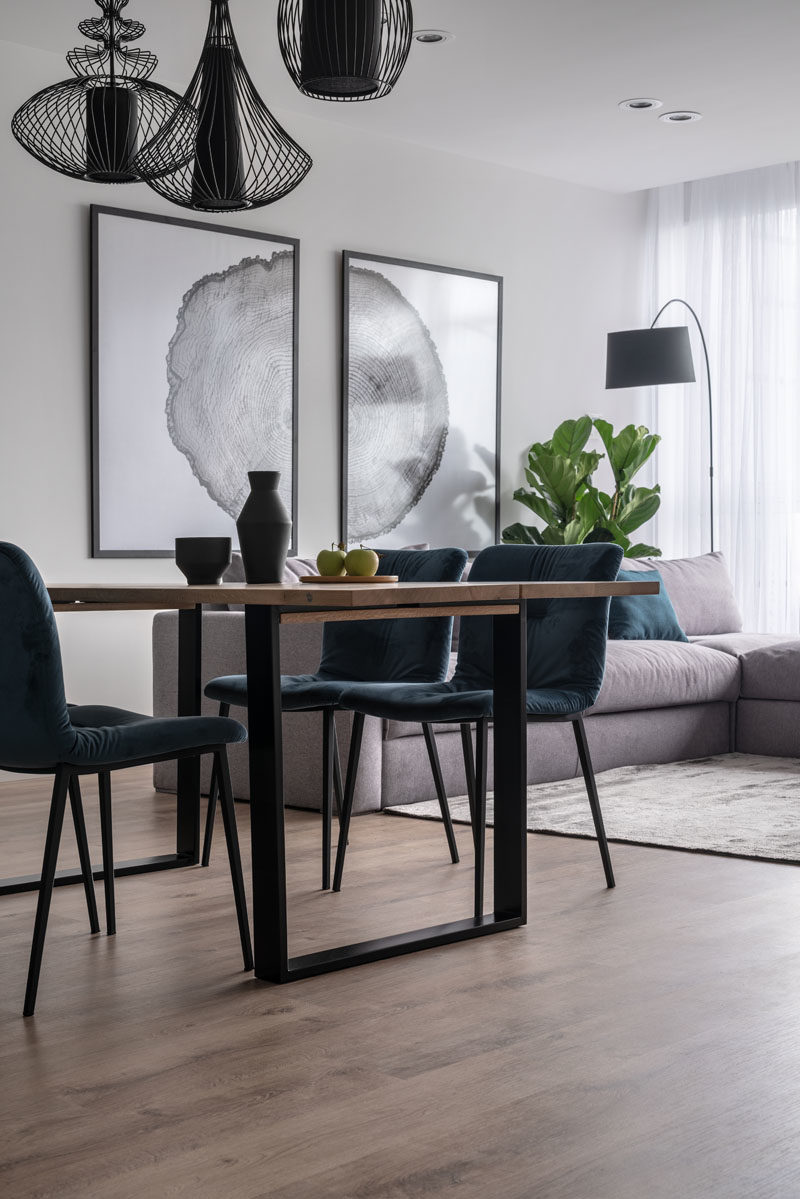 Dining Room Ideas - This modern dining area features three sculptural black pendant lights that anchor the table and chairs in the open plan room. #DiningRoomIdeas #DiningIdeas #InteriorDesign