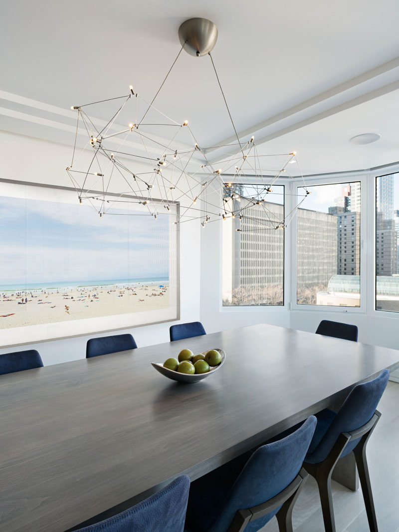 Dining Room Ideas - In this modern dining room, a curved section of windows provides views of the city, while a sculpture metal chandelier anchors the dining table in the space. #DiningRoomIdeas #ModernDiningRoom