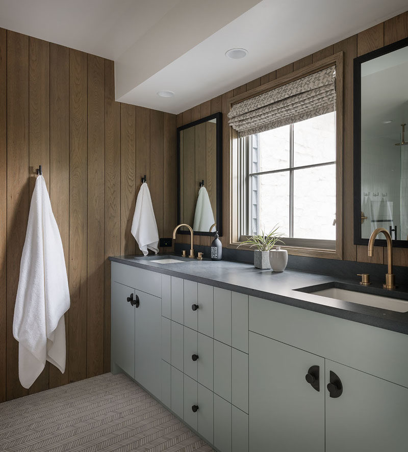 Bathroom Ideas - In this modern bathroom, the walls have been lined with wood and accented by black detailing, like the mirror frames, wall hooks, and cabinet hardware. #BathroomDesign #ModernBathroom