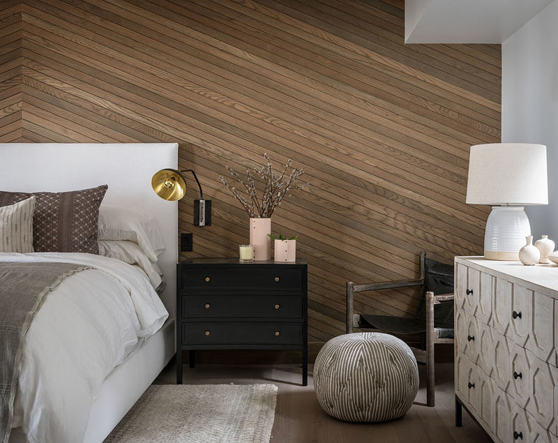 Bedroom Ideas - In this modern bedroom, an angled wood accent wall provides a natural touch to the room and adds a sense of warmth. #ModernBedroom #BedroomDesign #BedroomIdeas #WoodAccentWall