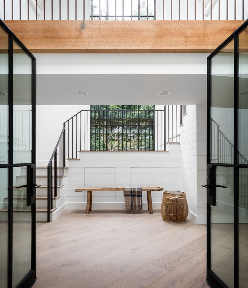 Black-framed glass doors welcome visitors to this modern farmhouse, where they'll find the entryway, and a view of an interior bridge.