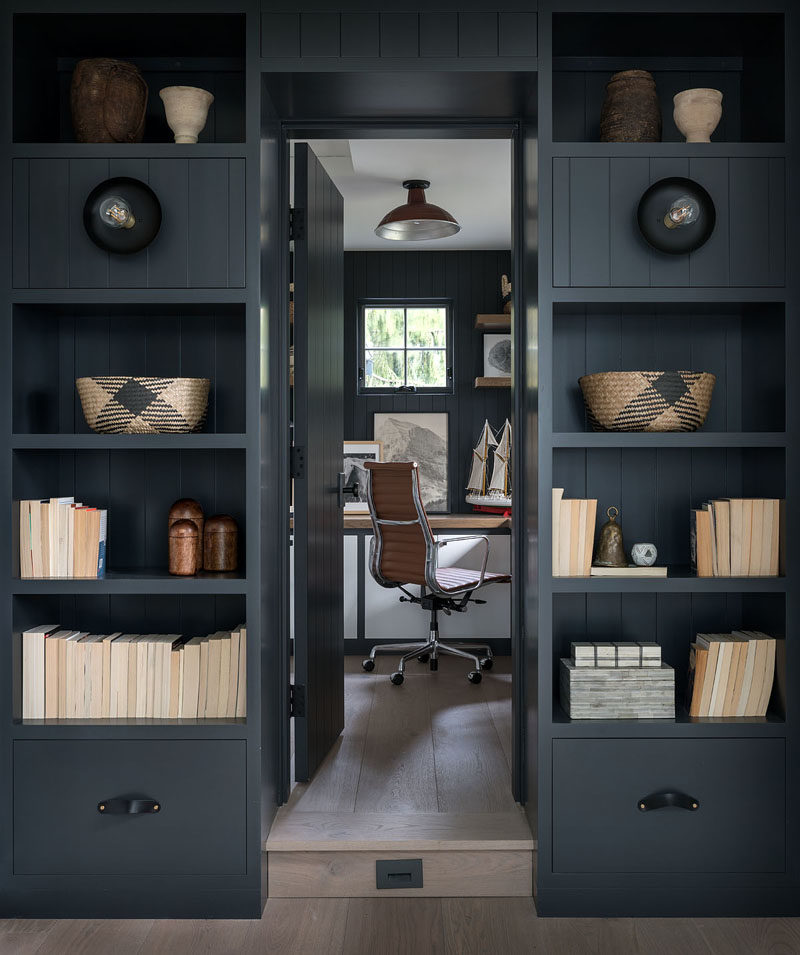 Home Office Ideas - Dark shelving surrounds a door that leads to the home office with matching dark walls. #HomeOfficeIdeas #ShelvingIdeas #HomeOffice #BookShelf