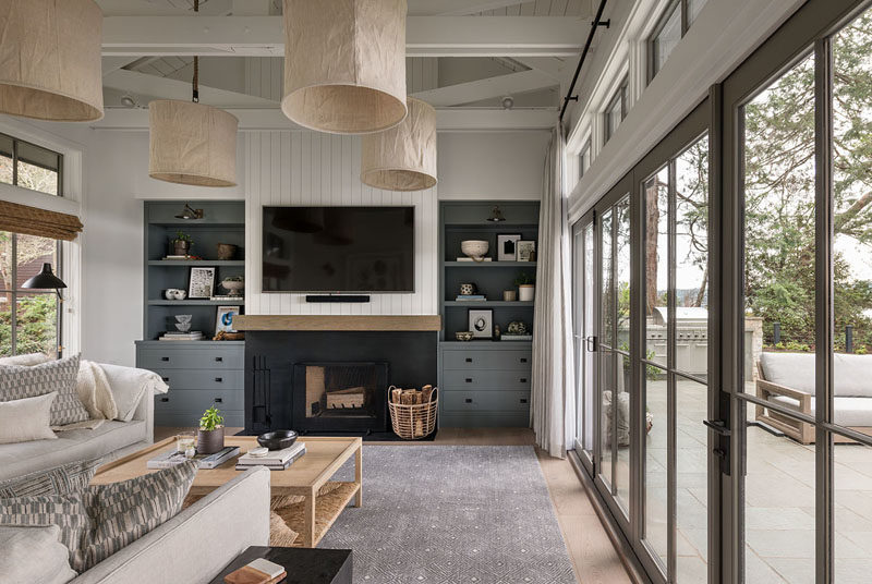 Living Room Ideas - This farmhouse modern living room has a fireplace with a television mounted above it, and built-in cabinetry on either side. #LivingRoomIdeas #ModernLivingROom #FarmhouseModern