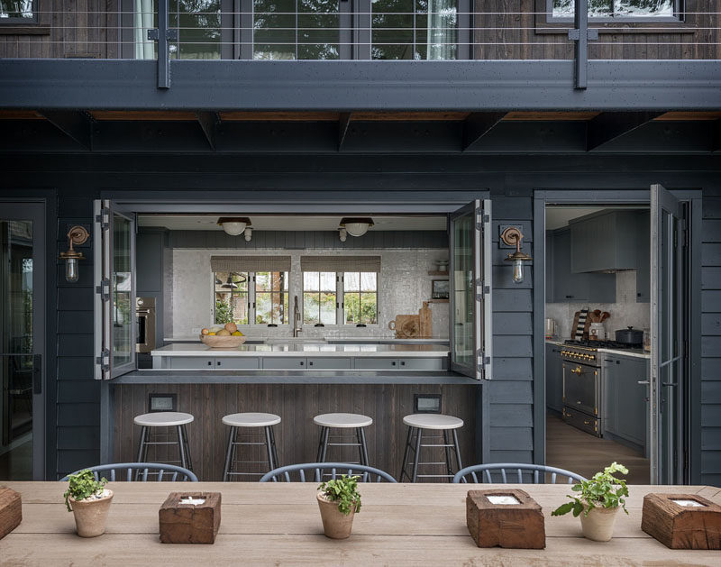 Folding windows in this modern kitchen open to reveal the bar that acts as a pass-through from the kitchen to the alfresco dining area. #FarmhouseModern #ModernFarmhouse #Kitchen #Bar