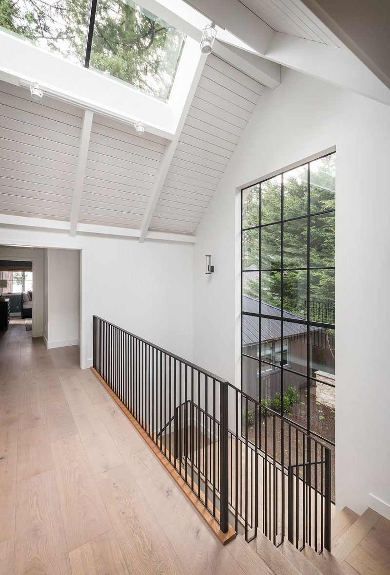 This modern farmhouse has an interior bridge, that's brightened by a skylight and a large section of windows, connects the home office with a casual entertaining room and bunk room. #Architecture #InteriorDesign #InteriorBridge #Skylight #Windows