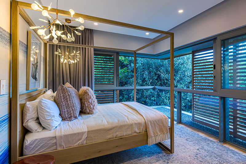 Bedroom Ideas - In this bedroom that features a modern four-poster bed, wood shutters provide privacy without blocking the surrounding tree views. #ModernBedroom #BedroomIdeas #WindowShutters #MasterBedroom