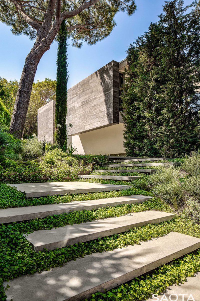 Landscaping Ideas - Welcoming visitors to this modern house is an entrance path with concrete steps that lead from the off-street parking below the house, through the garden, and to the front door. #Landscaping #ModernHouse #GardenSteps #ConcreteSteps