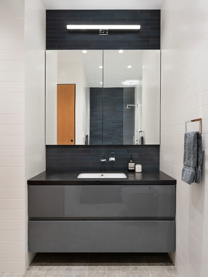 Bathroom Ideas - This modern bathroom features a glossy grey lacquer vanity, while dark skinny tiles laid horizontally contrast the white subway tiles. #BathroomIdeas #BathroomVanity #VanityIdeas #GreyCabinets #ModernBathroom