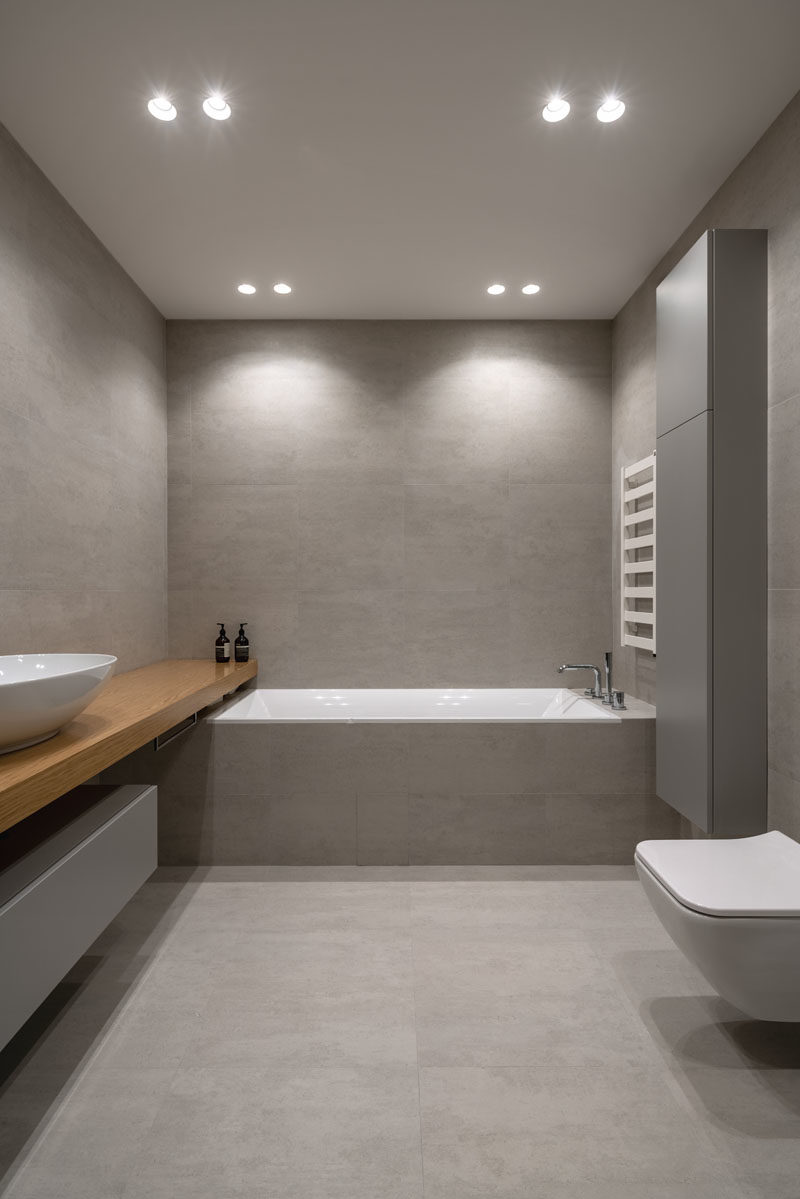 Bathroom Ideas - In this modern bathroom, large format grey tiles cover the walls and floor, while the  wood vanity adds a natural touch. #ModernBathroom #BathroomDesign #BathroomIdeas