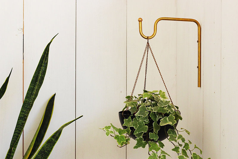 Decor Ideas - Tel Aviv based designer Yuval Tzur has created a modern hanging planter with a simple curved shape, and a matching brass wall hanger.  The planters are made from hand spun aluminum, that are then powder coated to create a durable finish suitable for both indoor and outdoor use. #HomeDecor #Planter #HangingPlanter #ModernPlanter #DecorIdeas