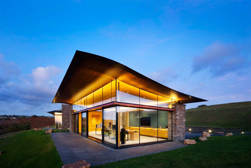 The design of this modern house includes a wave-like roofs that appears to 'float' above the walls of glass, while the stone work complements the surroundings and the traditional of dry stone walling found in Jersey. #ModernArchitecture #HouseDesign #GlassWalls #WavyRoof