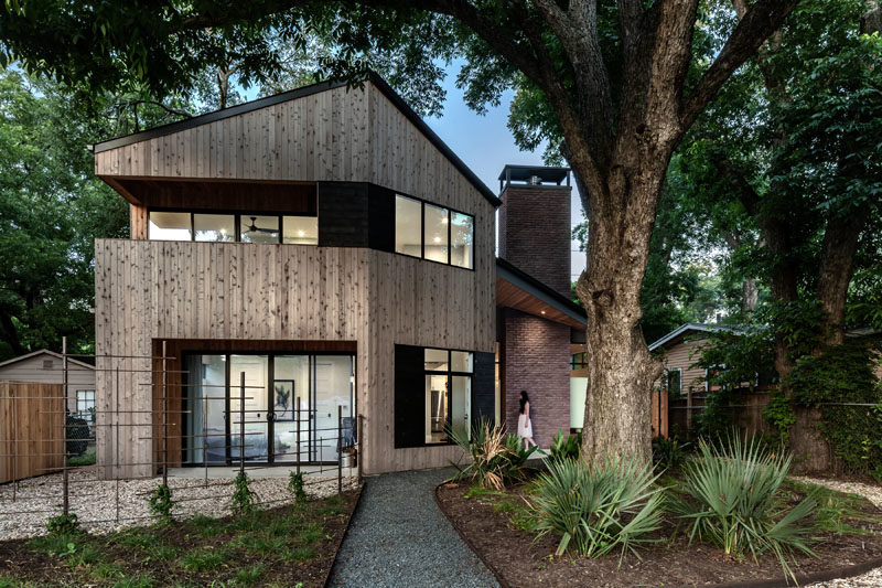 This modern house features materials like knotted cedar tongue & groove siding, brick, and dark gray stucco. #ModernHouse #HouseDesign #Architecture