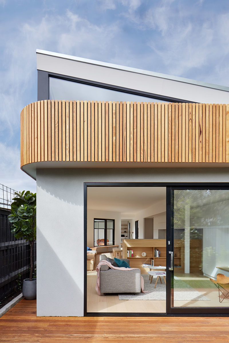 The exterior of this house extension features a curvaceous timber facade and a wood deck. Over time, the fences will be covered by climbers so the interiors will look out to a wall of green.  #Architecture #HouseExtension