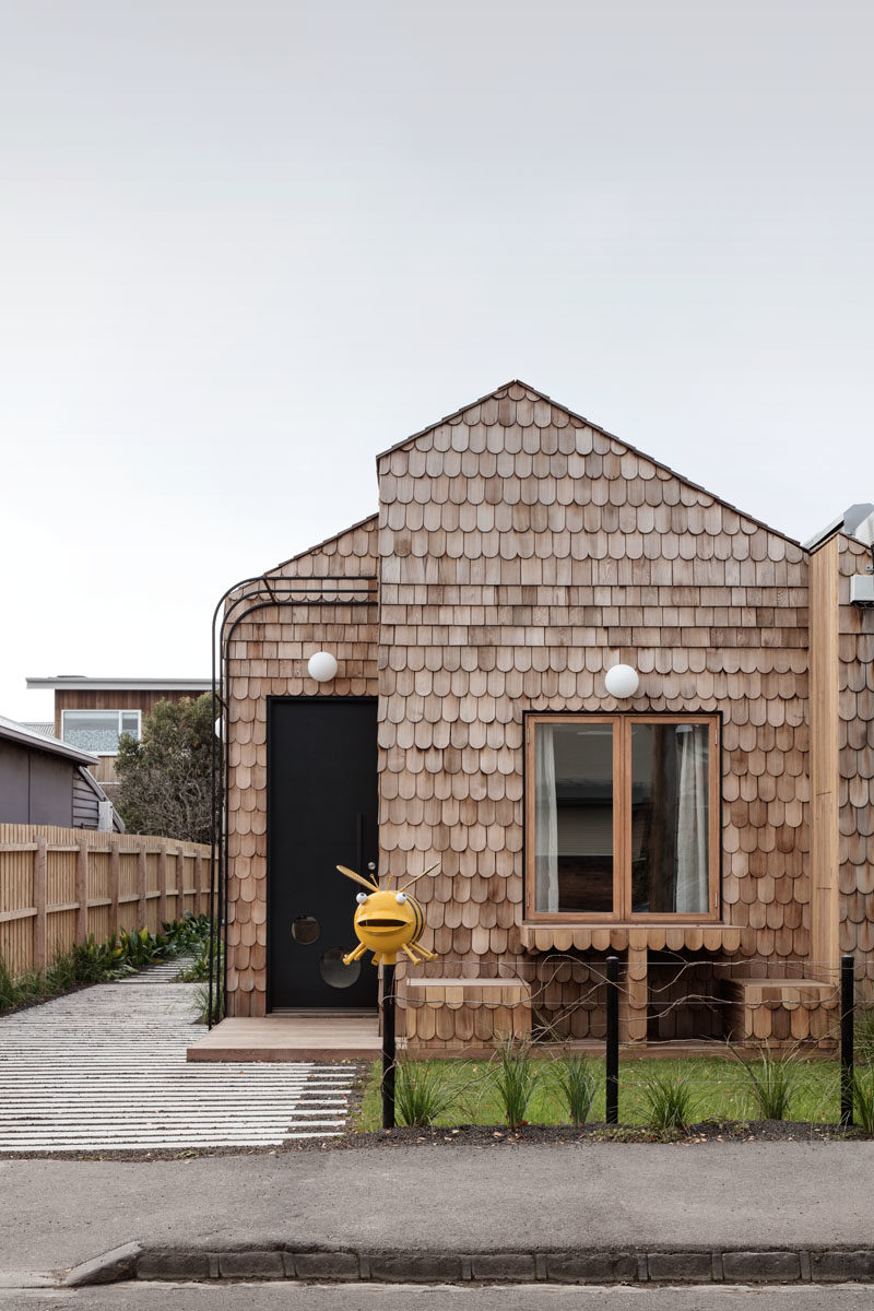 Mani Architecture has designed a modern cottage-like house in Melbourne, Australia, that's covered in wood shingles and features a built-in table and chairs in the front garden. #Shingles #ModernHouse #HouseDesign #Architecture