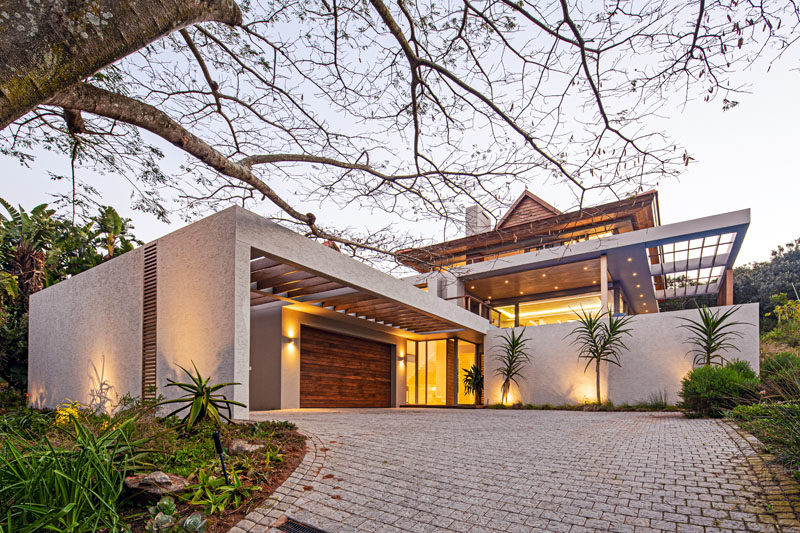 Drawing inspiration from tropical modern architecture, this house was designed to have an elemental roof form with large eaves, an overhanging upper storey, and indoor/outdoor living. #ModernHouse #HouseDesign #ModernArchitecture #TropicalModern