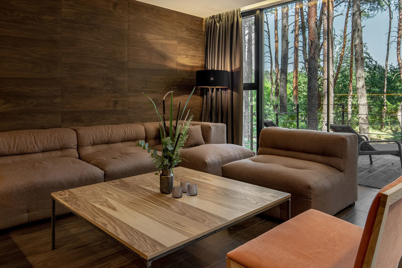Living Room Ideas - This modern living room has a wood accent wall to bring a natural touch inside, while floor-to-ceiling windows showcase the tree views. #LivingRoom #WoodAccentWall #LivingRoomIdeas