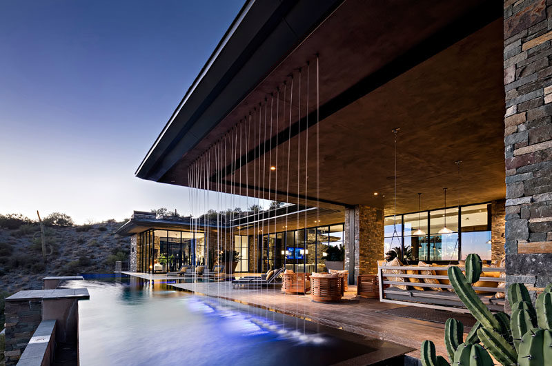 This modern house has a rainfall water feature that connects with the pool, and is located beside the outdoor living room, that also has a bbq and dining area. #SwimmingPool #Flooring #Architecture #OutdoorLivingRoom #Fireplace #WaterFeature