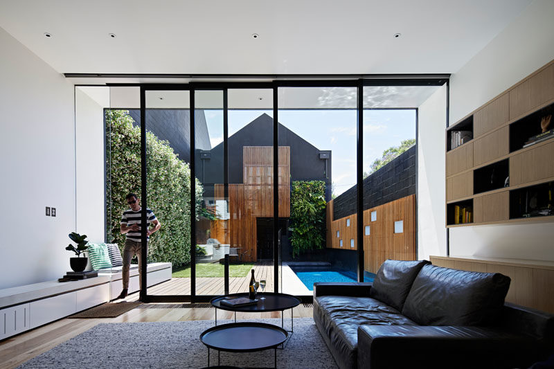This modern house has sliding glass doors that open the living room to the outdoor space, that features a patio, yard, green wall, and swimming pool. #GlassWall #SwimmingPool #LandscapeDesign