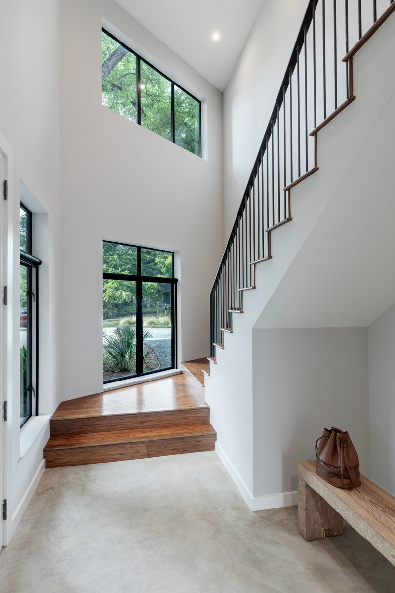 Stair Ideas - Wood stairs with black handrails connect the various levels of the home. #ModernStairs #StairDesign #StairIdeas