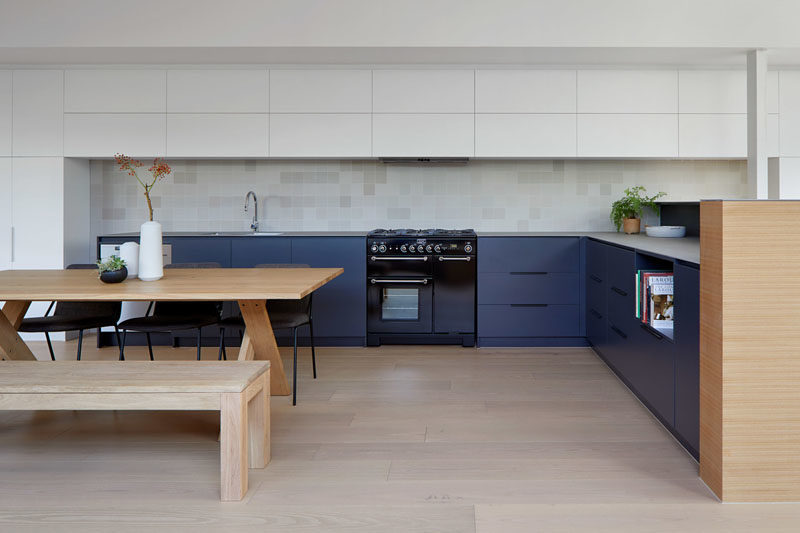 Kitchen Ideas - In this modern two-tone kitchen, dark blue cabinets have been used for the lowers, while minimalist white cabinets create additional storage and blend into the white walls. #ModernKitchen #KitchenDesign #KitchenIdeas