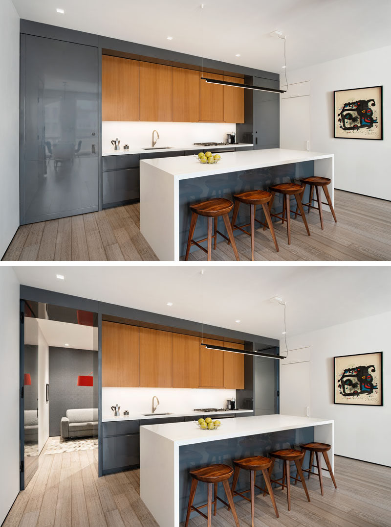 Kitchen Ideas - In this modern kitchen, high gloss gray lacquer cabinets have been used to complement the living room TV unit. The kitchen also features custom flush pivot doors on either end, built to look like part of the kitchen cabinetry. One of the doors reveals a hidden office, while the other leads to a guest bathroom. #KitchenIdeas #ModernKitchen #GreyCabinets #KitchenIsland