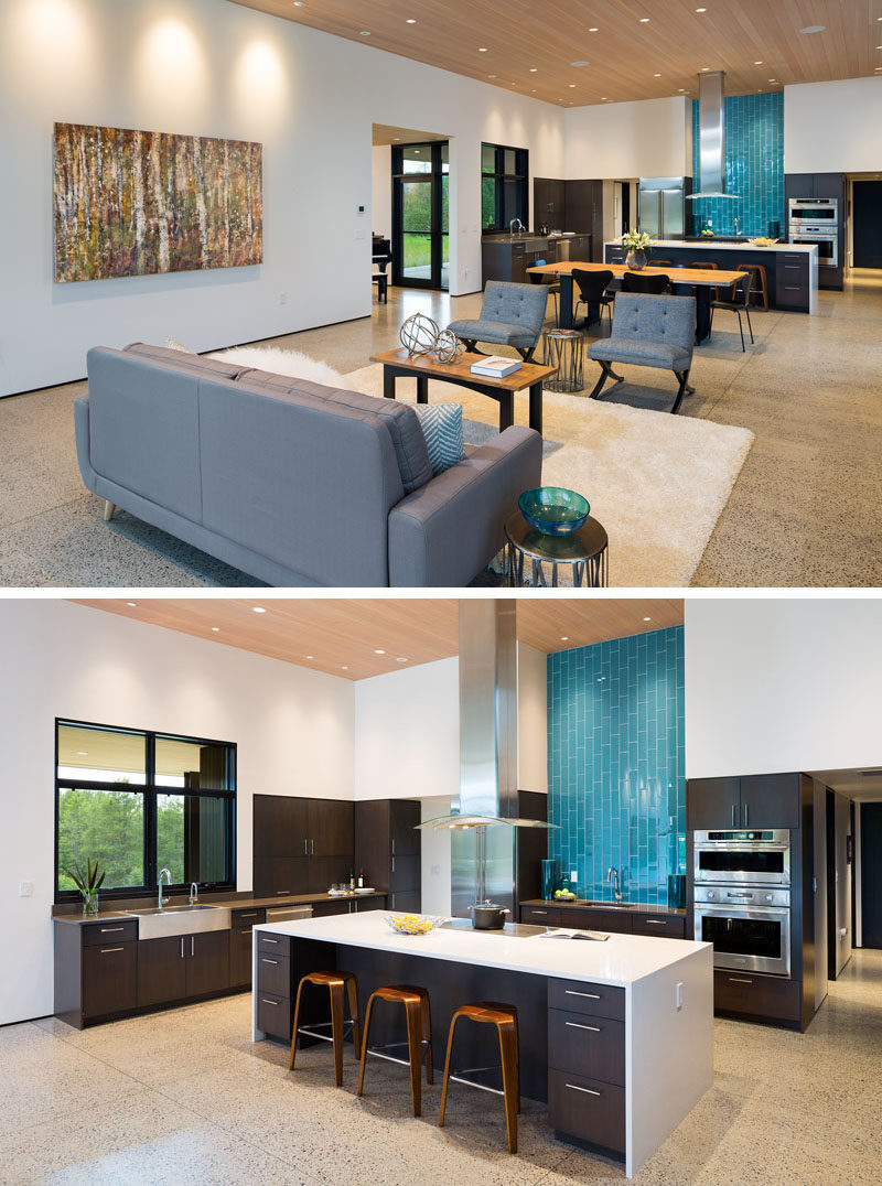 Kitchen Ideas - Blue tiles in this modern kitchen draw the eye to the opposite end of the open plan room, where a large island provides additional space for counter stools and storage. #ModernKitchen #KitchenDesign #KitchenIdeas #BlueBacksplash