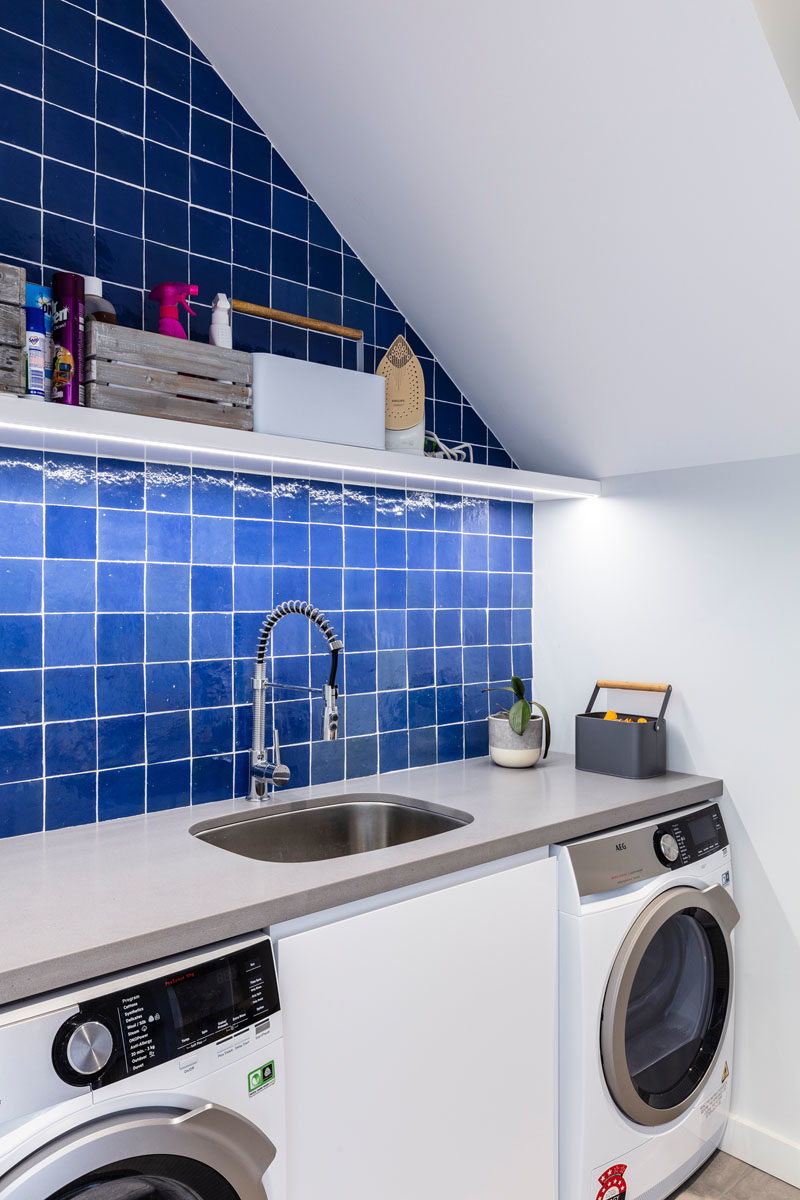 Laundry Room Ideas - This modern laundry room has a counter that runs across both the washing machine and dryer, while square blue tiles add some color and and upper shelf provides storage. #LaundryRoom #LaundryIdeas