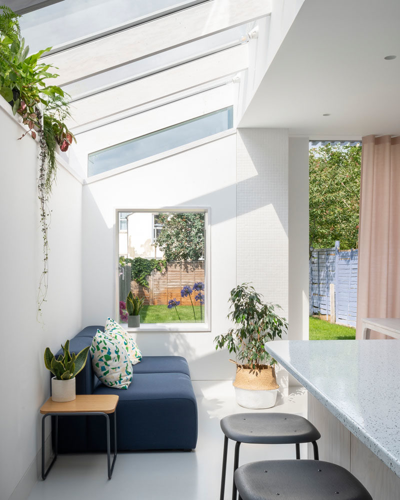 Inside this modern rear house extension, the material palette has been kept minimal with whitewashed Douglas Fir joinery and a seamless resin floor. The use of Douglas fir continues for the structural fins and window reveals, while a plant shelf runs the length of the extension and takes advantage of the light from the windows. #WhitewashedWood #ModernInterior #PlantShelf #Windows #RearExtension #HouseExtension