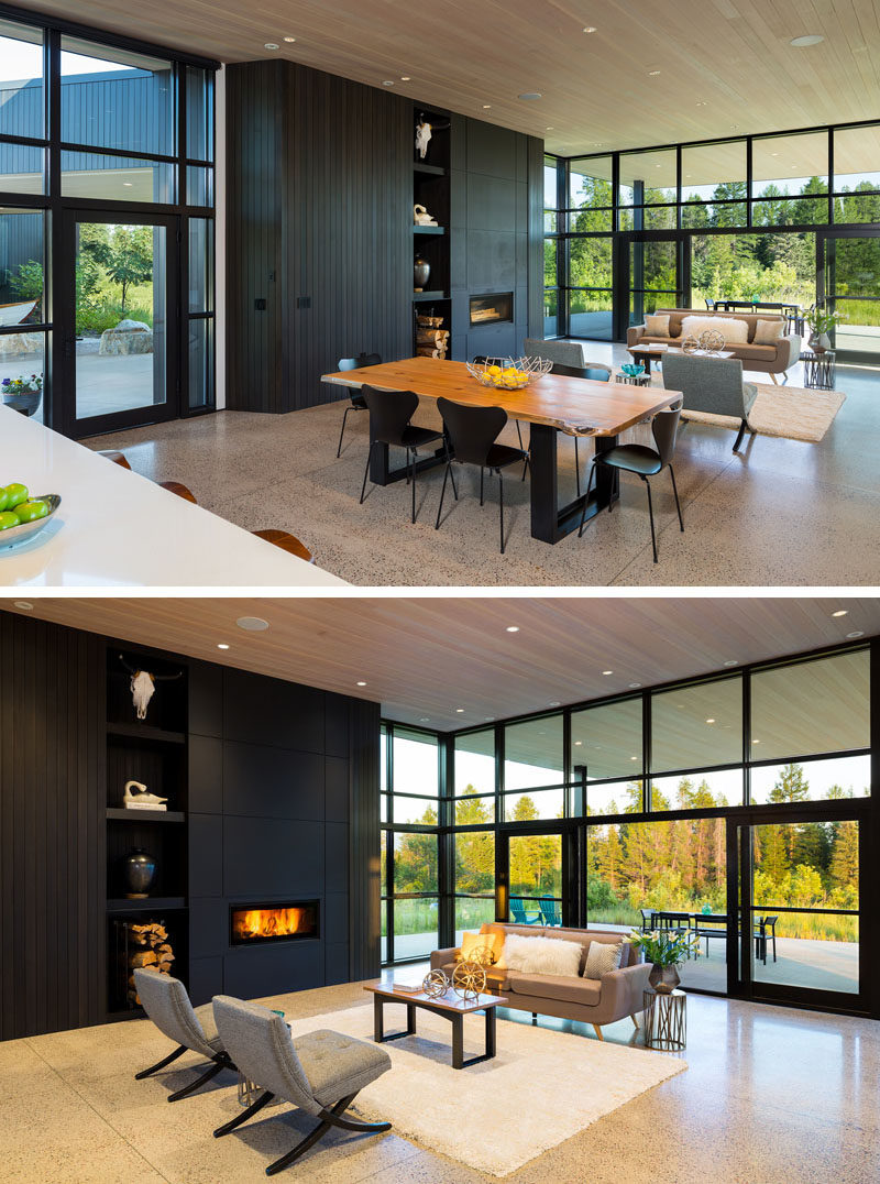 Living Room Ideas - Inside this modern house, the floor plan has been kept open, allowing the living room, dining room, and kitchen, to share the space, and take advantage of the natural light from the floor-to-ceiling windows. #ModernHouse #LivingRoom #BlackFireplace #GlassWalls