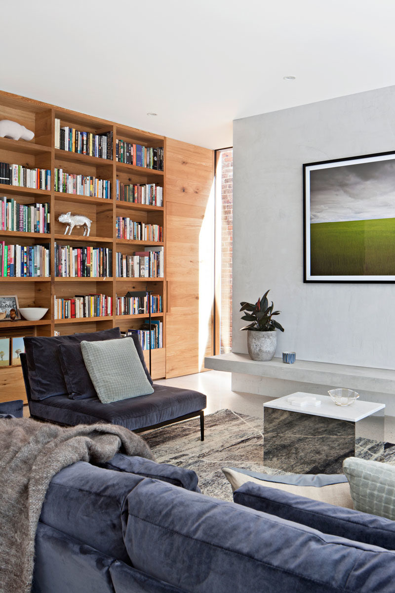 Bookshelf Ideas - In this modern living room, a built-in wood bookshelf lines the wall, and adds a warmth to the room. #BookshelfIdeas #ModernLivingRoom