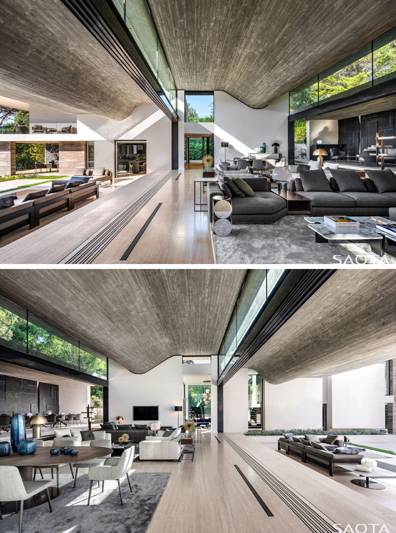 Clerestory windows fill this modern house with natural light, provide views of the trees, and draw the eye upwards to the wavy concrete ceilings. #Windows #ClerestoryWindows #WindowIdeas #ConcreteCeiling #InteriorDesign