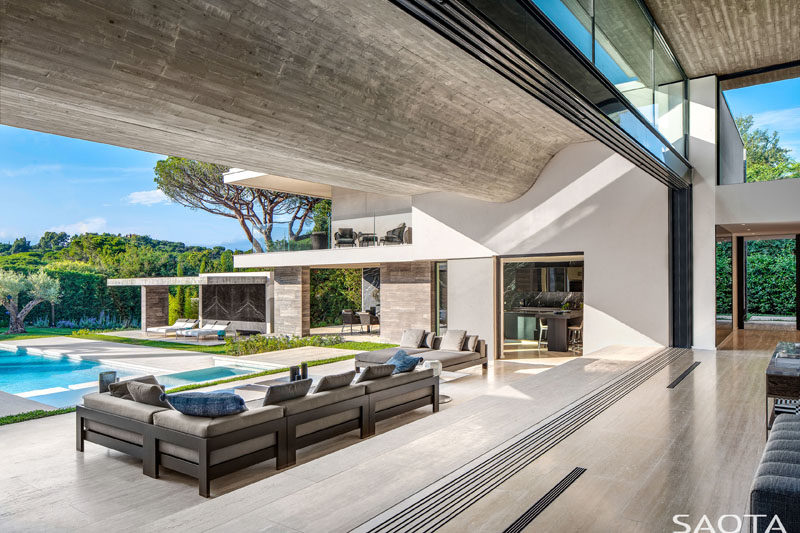 Glass cavity doors slide open to create an indoor/outdoor living experience for this modern home, and allow the cool summer breezes to flow through the house. #GlassWalls #IndoorOutdoor #ModernHouse