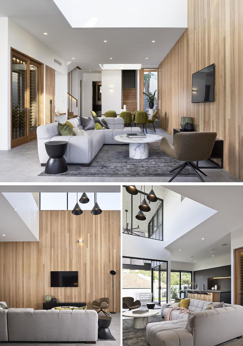 Living Room Ideas - A wood accent wall connects the dining area and living room in this modern house. A void above the living room is filled with multiple pendant lights, while a skylight adds natural light during the day. #LivingRoomIdeas #ModernLivingRoom #WoodAccentWall