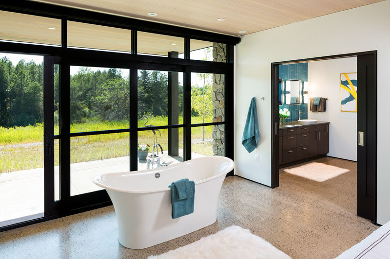 In this modern bedroom, a freestanding bathtub takes center-stage, with it positioned in front of the windows.  #FreestandingBathtub