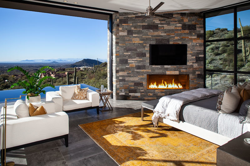 Bathroom Ideas - This modern master bedroom has sweeping views of the valley, a sitting area, and a fireplace in the corner adding warmth on cool nights. #BedroomIdeas #MasterBedroom #Fireplace