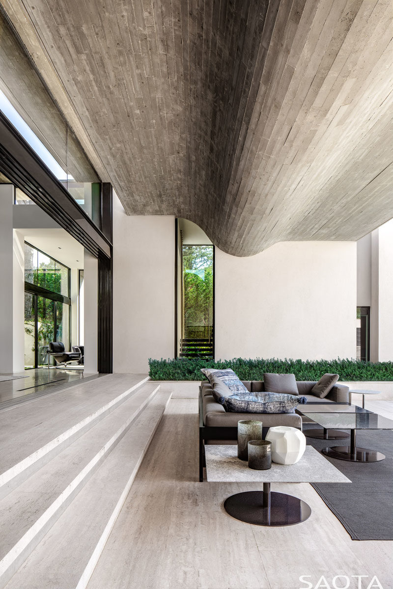 The main living areas of this modern house step down to the landscaped terrace. Throughout the home, vein cut Travertine floors have been featured, while the ceiling features a wavy concrete element. #ModernHouse #ConcreteCeiling #TravertineFloors