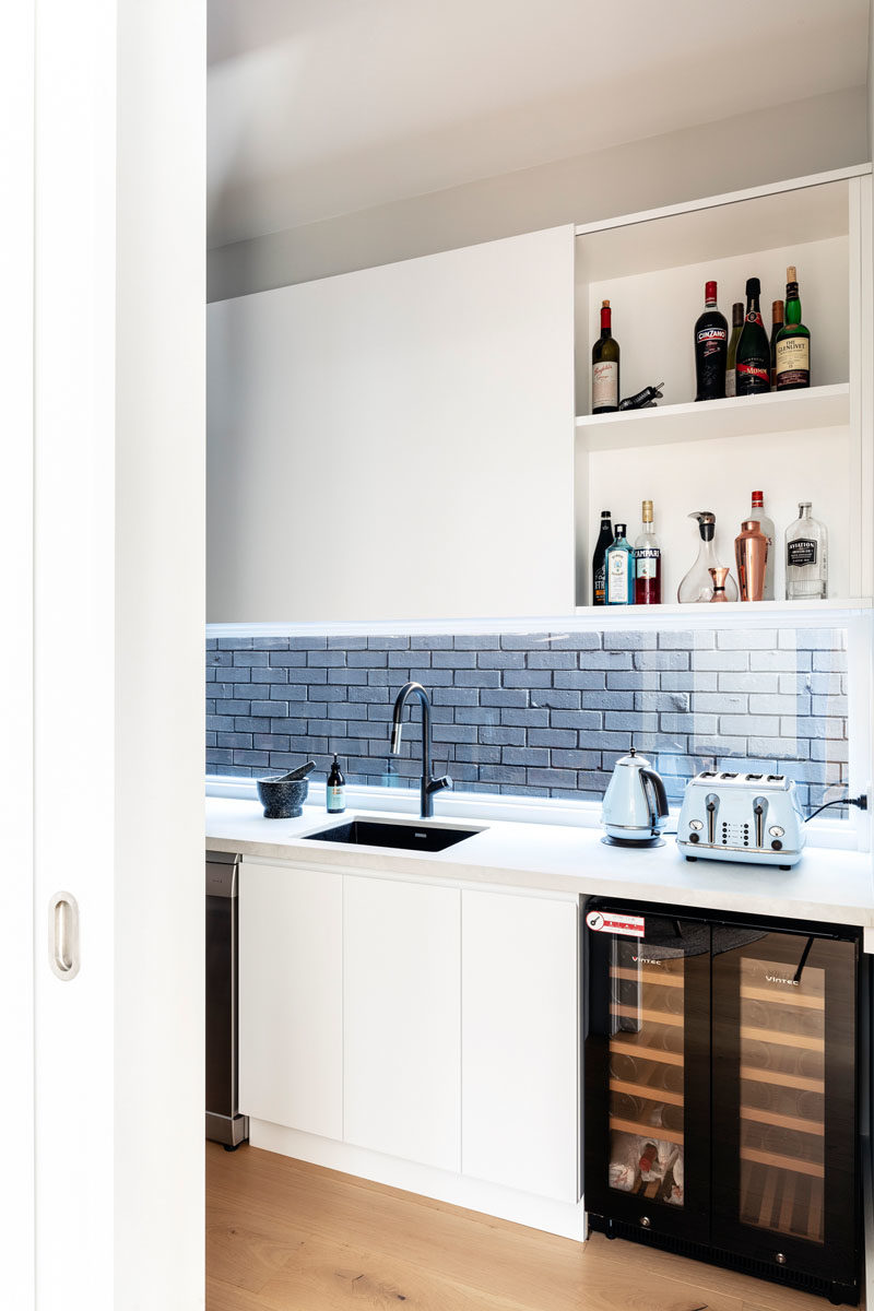 Pantry Ideas - This modern kitchen pantry has plenty of storage, a sink, counter space, and a bar area. #KitchenPantry #PantryIdeas
