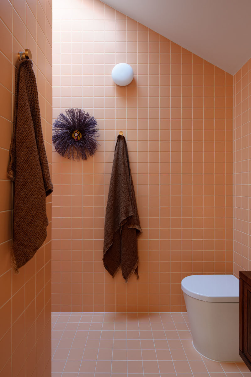 Bathroom Ideas - This modern ensuite bathroom has been covered in peach colored tiles, and features with an angled ceiling. The shower is located around the corner, directly beneath a skylight. #ModernBathroom #BathroomIdea #SquareTiles #PeachTiles #BathroomDesign