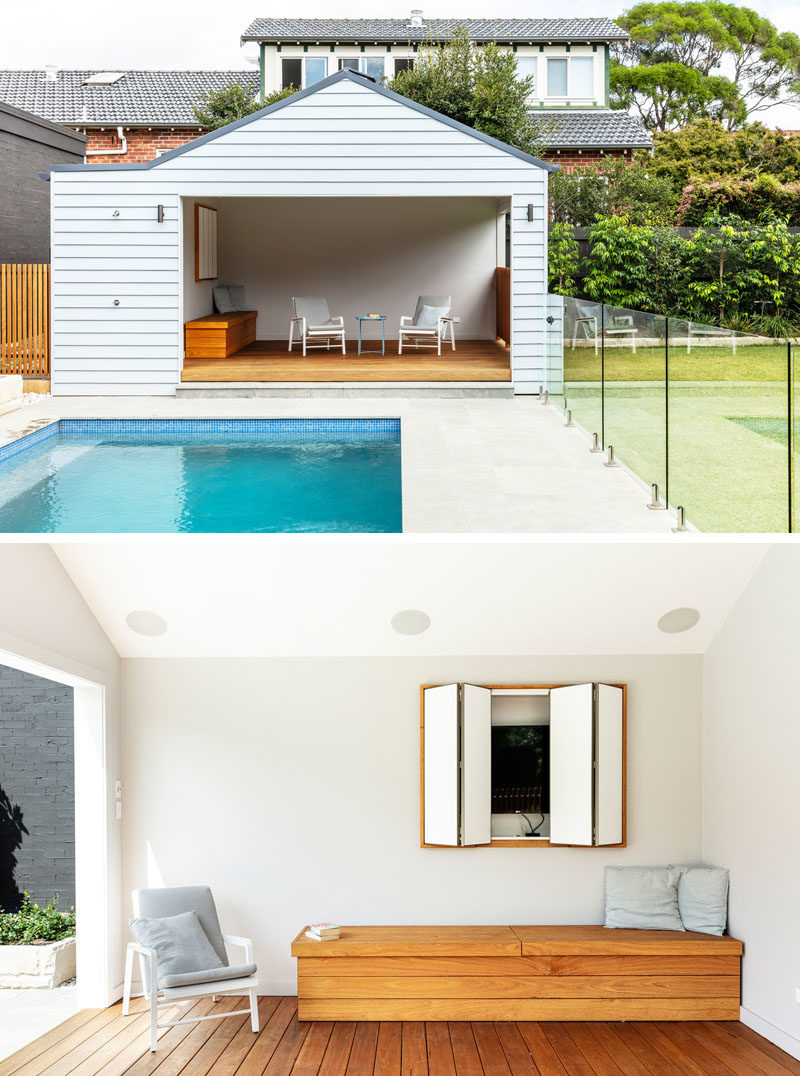 Swimming Pool Ideas - A swimming pool, surrounded by a glass safety fence sits next to a grassy lawn, while a cabana provides shade on a sunny day. #SwimmingPoolIdeas #SwimmingPool #Cabana