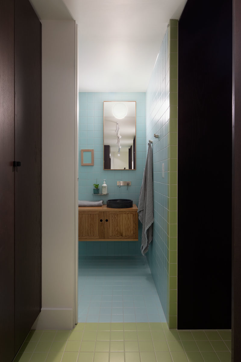Powder Room Ideas - This modern powder room hidden behind a pocket door, features pastel blue tiles that cover the walls and floors. #PowderRoomIdeas #ModernPowderRoom #BathroomDesign #BlueTiles