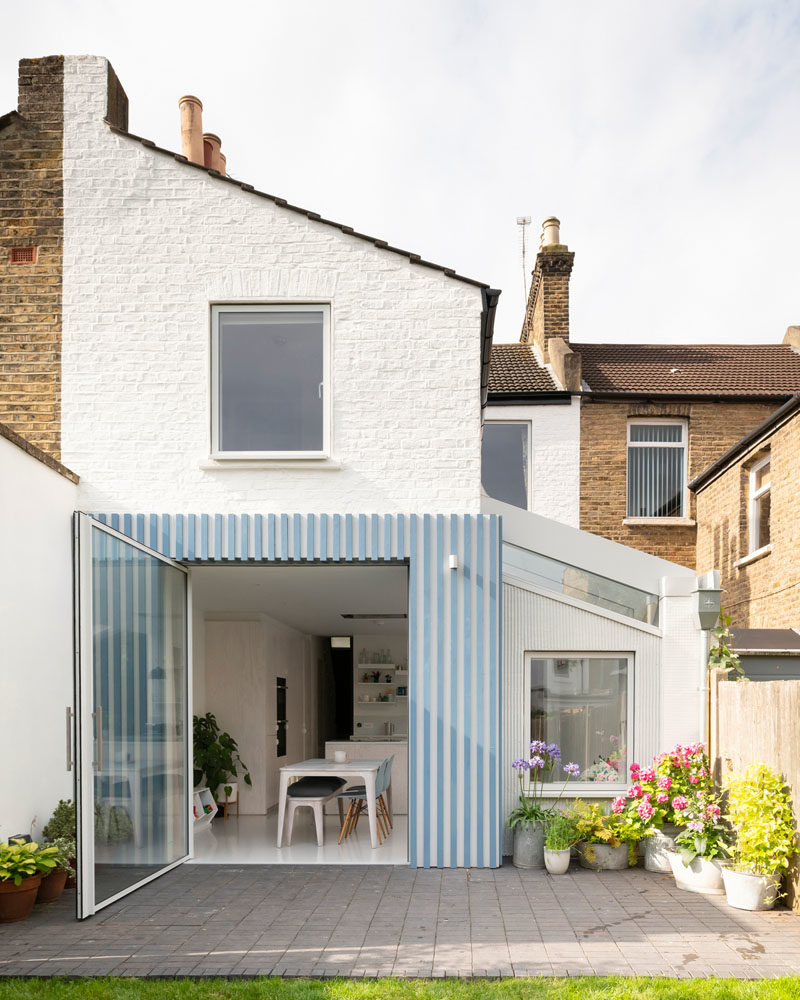 This new and modern rear extension features a glazed roof that brings in light, while the floor throughout the rear of the house was lowered to provide additional head height and a consistent level with the new patio. A large pivoting door allows unobstructed views of the garden, visually extending the space, and providing an easy way to access the yard. #RearExtension #HouseDesign #HouseExtension #PivotingDoor